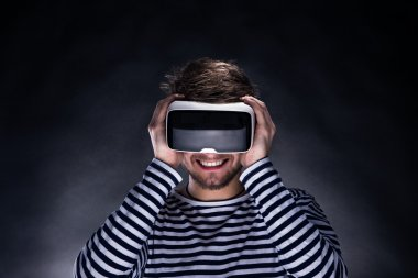 Man wearing virtual reality goggles. Studio shot, black backgrou