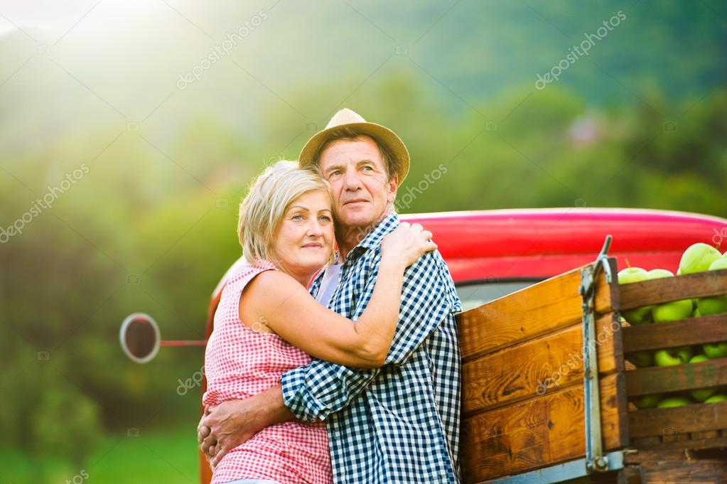 Senior couple in nature at vintage car