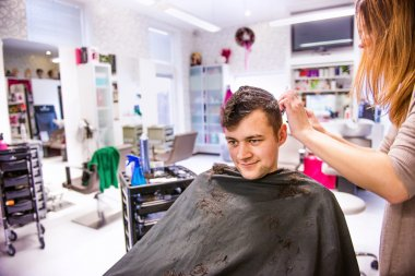 hairdresser cutting hair of young client.