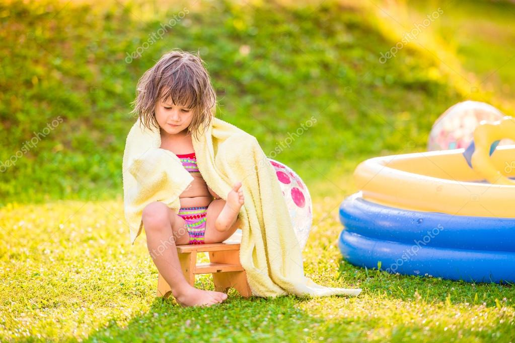 Girl in towel sitting by swimming pool