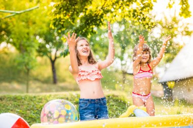 Two girls splashing water, sunny summer in the garden