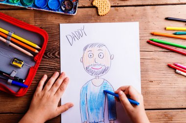 girl drawing picture of her father.