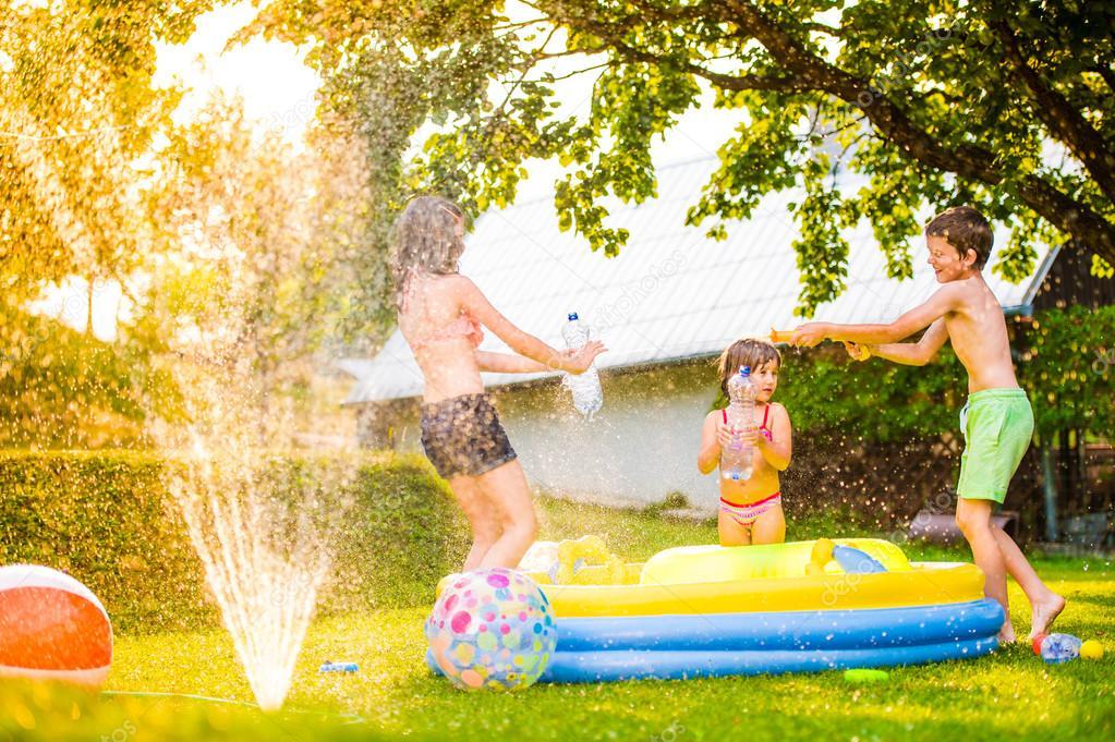 Boy splashing girls with water gun
