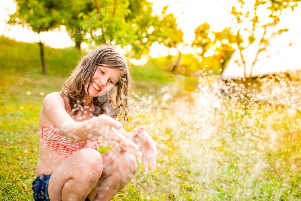 Girl in bikini sitting at sprinkler