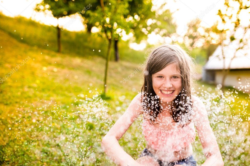 Girl in bikini sitting at the sprinkler