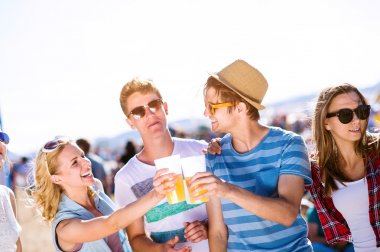 Group of teenage boys and girls with beers in a crowd at summer music festival, , sunny day stock vector