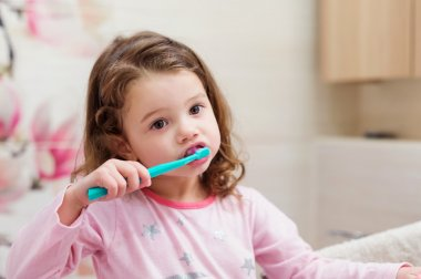 Little girl in pink pyjamas in bathroom brushing teeth