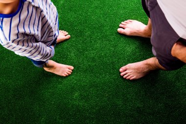 father and son standing on artificial grass