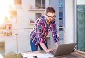 Fotografie Businessman working from home on laptop, standing on balcony