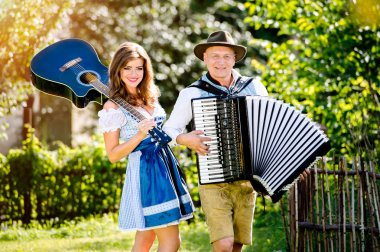 Couple in traditional bavarian clothes with guitar and accordion