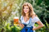 Frau in bayerischer Tracht mit Bier