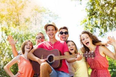 Friends with guitar having fun