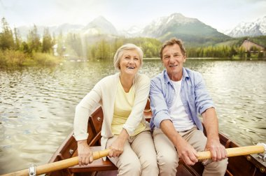 Senior couple paddling on boat