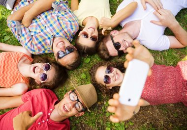 People lying on the grass and taking selfie
