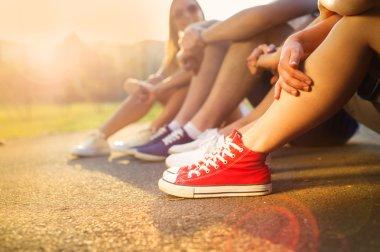 Boys and girls sitting on the sidewalk