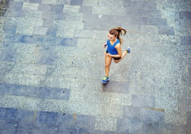 Female runner jogging on tiled pavement