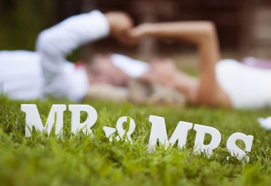 Bride and groom lying on grass