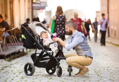 Man with beard walking with baby in pram