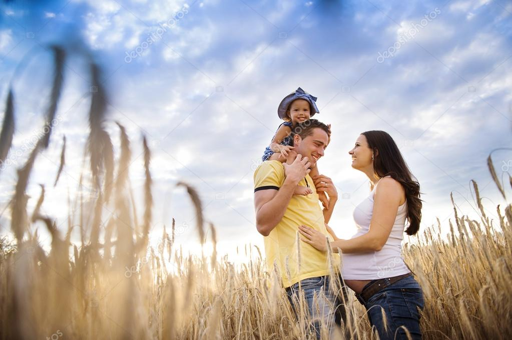 Pregnant family with daughter in  field