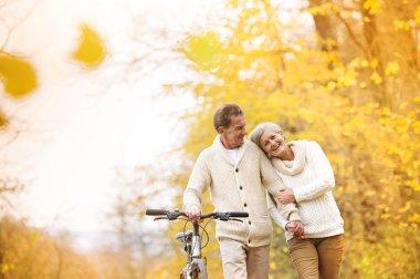 Senior couple enjoying walk with bicycle