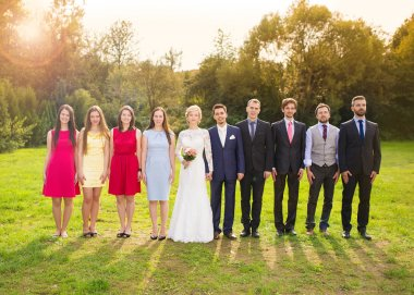 Bridesmaids and groomsmen in sunny park