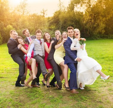 Newlywed couple having fun with bridesmaids and groomsmen