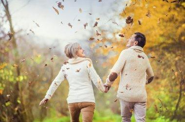 Active seniors having fun in autumn forest