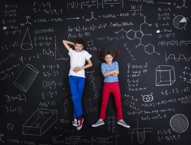 Boy and girl learning in front of a blackboard