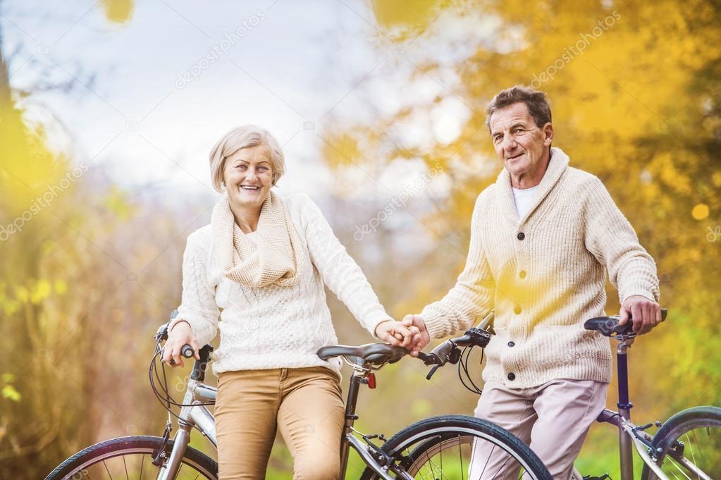 Active seniors on bikes in autumn nature stock vector