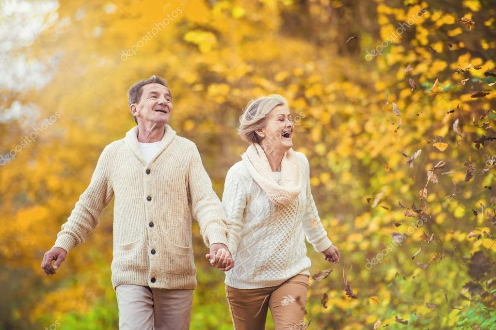 Active seniors having fun in autumn forest