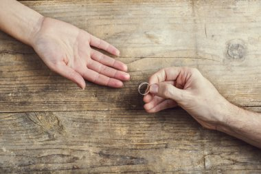 Man putting on engagement ring tenderly to his woman