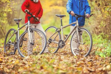 Active senior couple having walk with bikes in autumn nature. details of legs and bikes  on fallen leaves stock vector