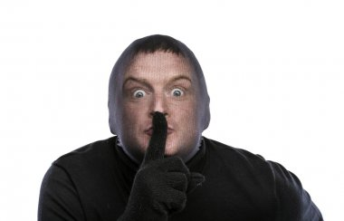 Thief in balaclava gesturing silence sign