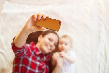 Little baby girl and her mother taking selfie