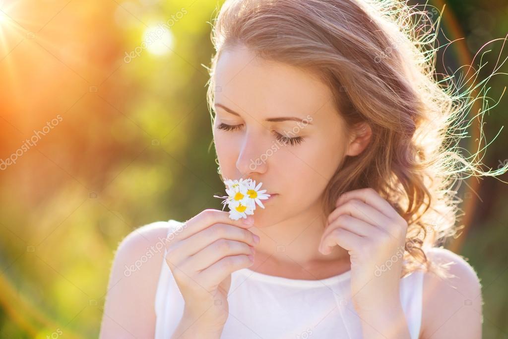 40f5e043b93 Γυναίκα μυρίζοντας λουλούδια σε ένα λιβάδι. — Φωτογραφία Αρχείου ...