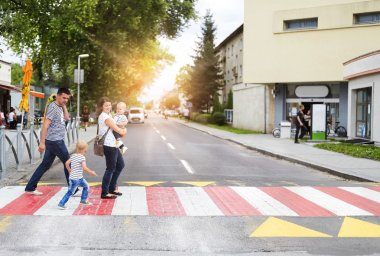 Young family walking on a crosswalk