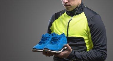 Runner holding blue running shoes.