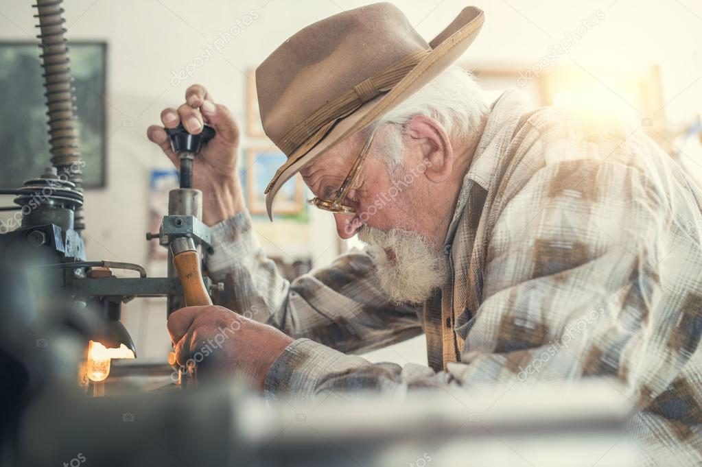 Senior man carving letters