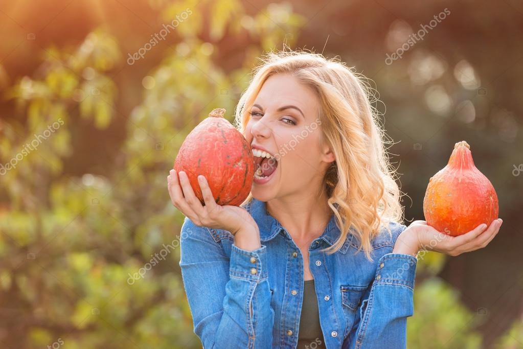 Beautiful woman harvesting pumpkins
