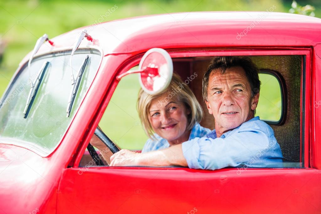 Senior couple in red car