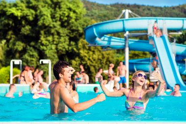 Young couple in swimming pool on sunny day. Water slide.