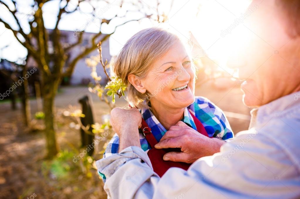 Senior man adjusting womans apron, elderly couple, sunny garden,
