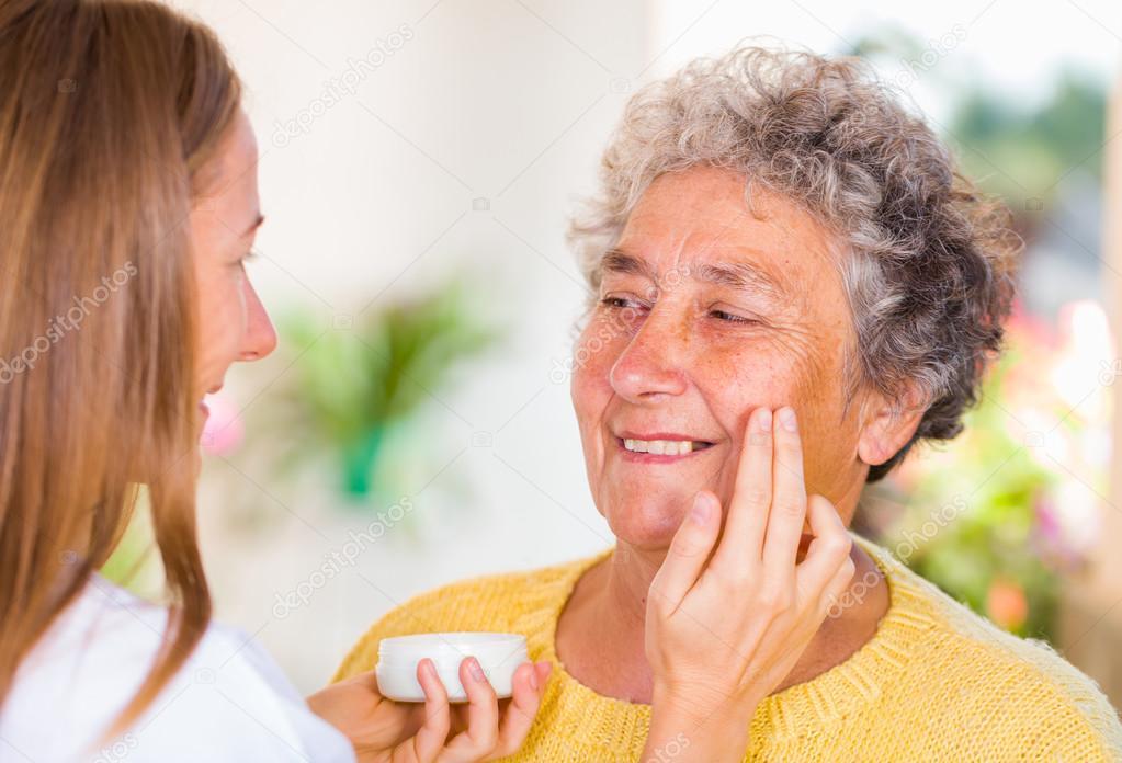Caregiver rubs the face cream on the elderly womans face — Foto de obencem