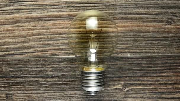 lampadina incandescente su fondo di legno marrone. Molte lampade e illumina in uno solo. concetto di idee