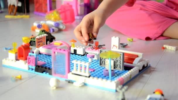 Kis gyerek játék, sok-sok színes műanyag blokkok fedett. A gyerekek játszani. Gyermekek napközbeni ellátása. Gyermek és játékok