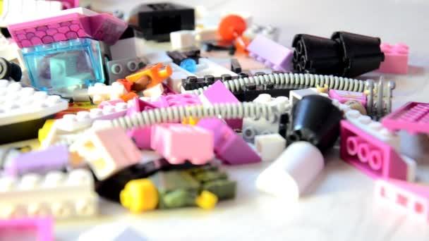 Sok színes műanyag blokkok. Tervező gyermekek különböző részein. A kamera mozog, gyorsan