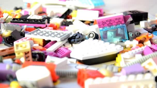 Spousta barevných plastových bloků. Mnoho různých částí dětí návrháře. Kamera se pohybuje pomalu