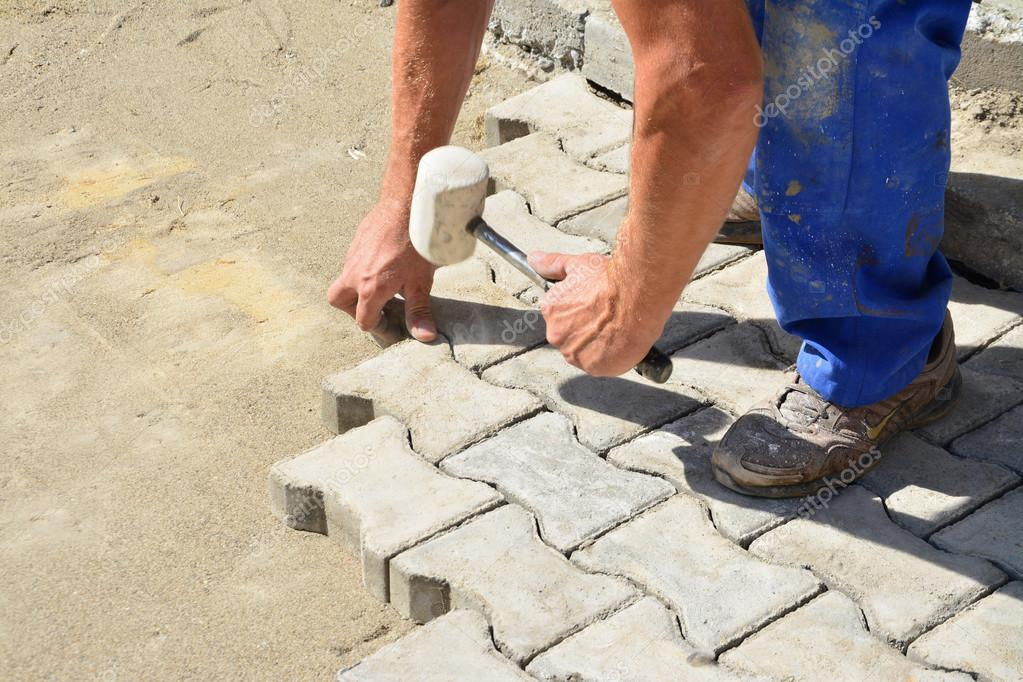 worker laying interlocking pavers stock photo. Black Bedroom Furniture Sets. Home Design Ideas