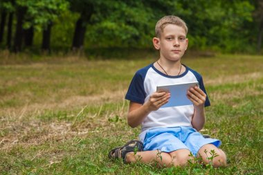 Cute young caucasian kid working with tablet in park.