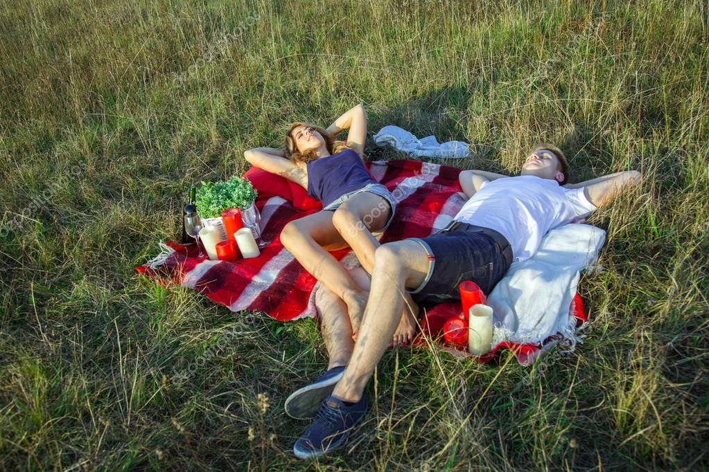 Young lovely couple lying down on summer days picnic.